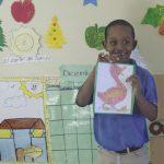 Stolzer Schüler der Idene-Schule mit selbstgemaltem Bild in der Hand