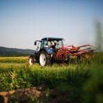 Der Landwirt auf dem Traktor bei der Arbeit auf dem Feld