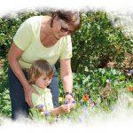 Frau und Kind betrachten Blüte einer Blume