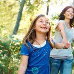 Frau und Kind spazieren fröhlich in der Natur