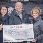 Mitarbeiterin der Bäckerei K&U übergibt Spendenscheck an Jörg Breiholz und Daniela Schmidle von der Diakonie Lörrach.
