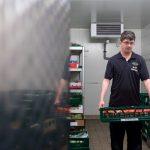 Der behinderte Mitarbeiter Marcel holt frisches Obst und Gemüse aus dem Lager des EDEKA-Marktes.