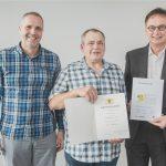 Jürgen Sinn (r.), Geschäftsführer von EDEKA Südwest Fleisch, und Klaus Schmitt (l.), Betriebsleiter Logistik in Rheinstetten, gratulierten dem Jubilar Günther Wussler.