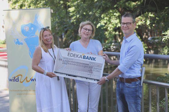 Der symbolische Spendenscheck wird von Christhard Deutscher, Pressesprecher von EDEKA Südwest, an den Verein Wildwasser e.V. übergeben.